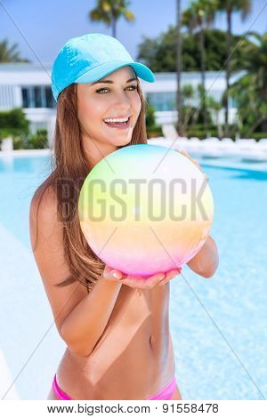 Happy woman with ball in swimming pool, having fun on beach resort, enjoying summer activity, playing water game, vacation and enjoyment concept