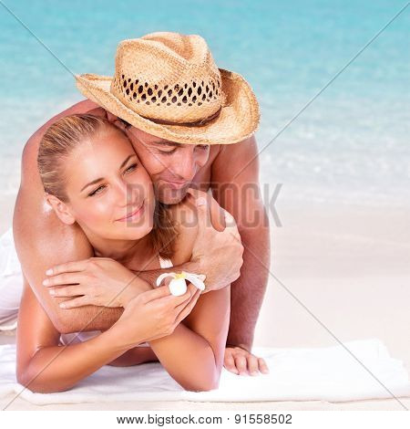 Happy couple lying down and hugging on the beautiful sandy beach, enjoying each other, spending honeymoon vacation, summer activity concept