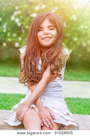 Portrait of a cute little girl sitting in the park and enjoying bright sunny day, having fun outdoors, spending time in daycare at summer camp, happy childhood concept