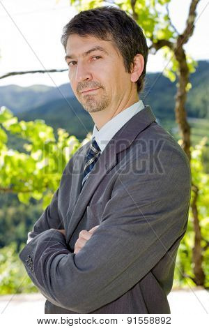portrait of a young businessman thinking, outdoors