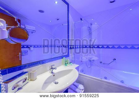 Fragment of a luxury bathroom in blue light.