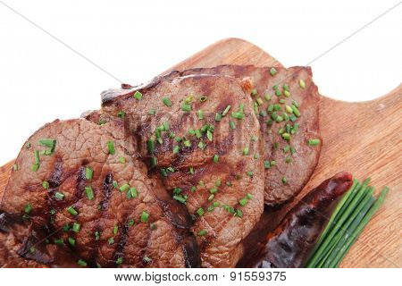 roasted beef meat fillet on wooden plate with thyme and chives isolated on white background