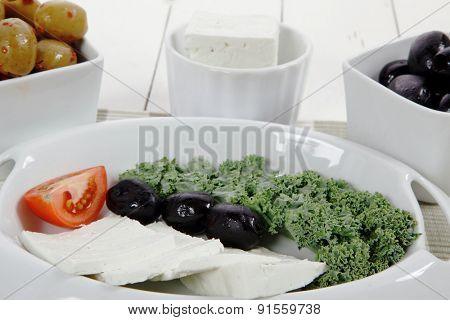 fresh greek feta cheese sandwich on white plate with hot green olives and black, goat cheese cube, tomatoes kale over retro table