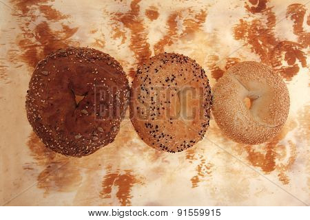three different fresh bagels  over baking paper as background