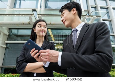 Businesswoman discuss something with businessman on cellphone
