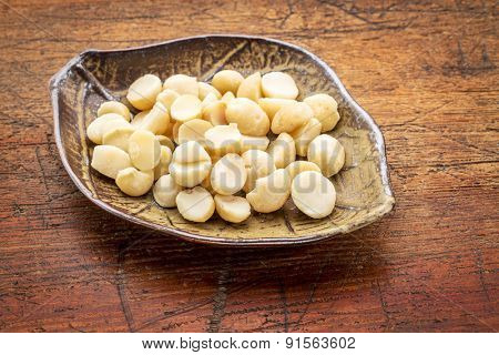 macadamia nuts on a ceramic leafs shaped bowl against rustic wood