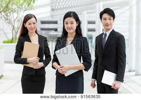 Business teammate with holding laptop, tablet and clipboard