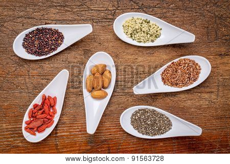 superfood grain, seed, berry, and nuts  abstract - top view of spoon bowls against rustic wood