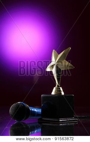 star trophy and microphone  on the purple background