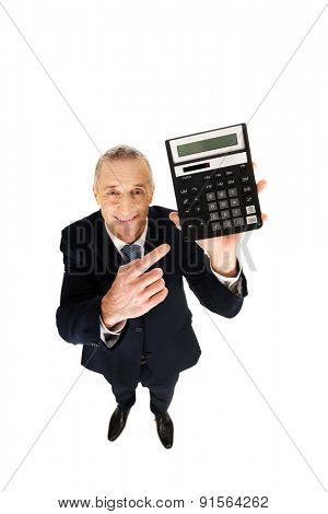 Happy businessman pointing on calculator.