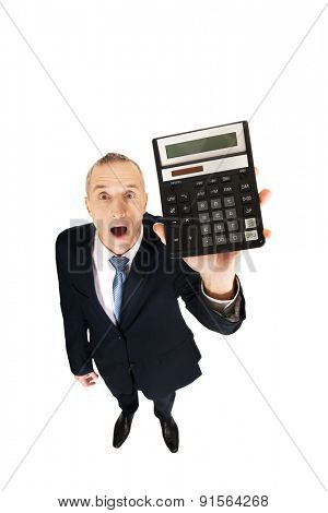 Surprised mature businessman holding a calculator.
