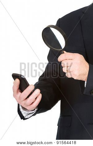 Closeup on businessman with magnifying glass.