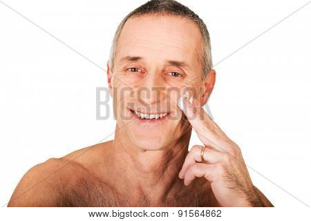 Portrait of a man applying cream on his face.