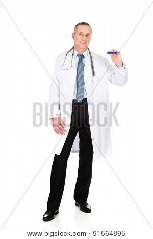 Full length male doctor holding a thermometer.