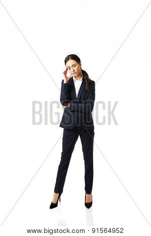 Full length businesswoman tired because of troubles holding her head.