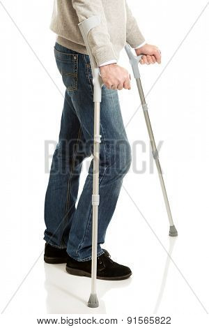 Close up on male legs with crutches.