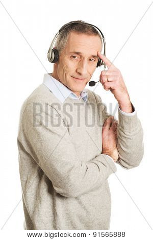 Call center man wearing a headset touching head.