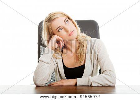 Thoughtful woman sitting at the desk touching chin.