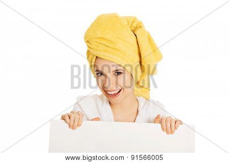 Portrait of woman in bathrobe holding empty banner.