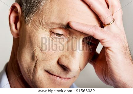 Portrait of depressed mature man touching his head.