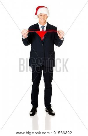 Full length santa businessman holding female thongs.