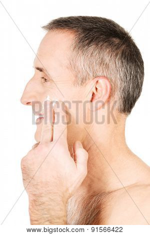Side view of a man applying cream on his face.