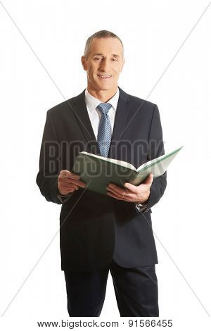 Businessman reading his note book.
