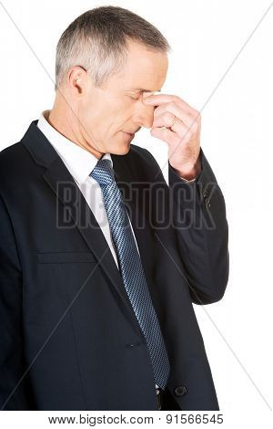 Portrait of businessman suffering from sinus pain.