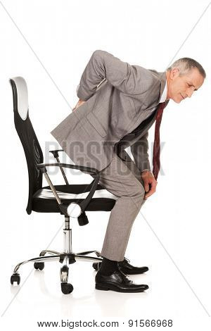 Businessman with backache standing up from a chair.