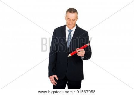 Manager writing with an oversized red pencil.