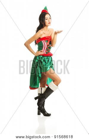 Full length woman wearing elf clothes blowing a kiss.