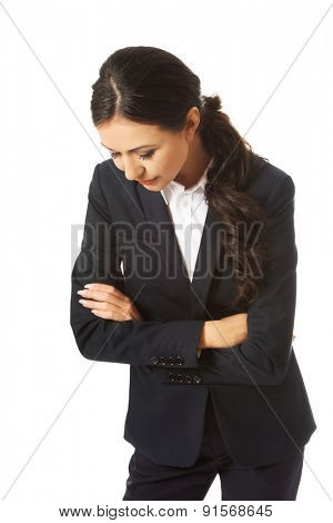 Pensive businesswoman with folded arms looking down.