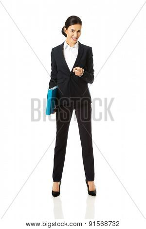 Businesswoman with binder pointing on you.
