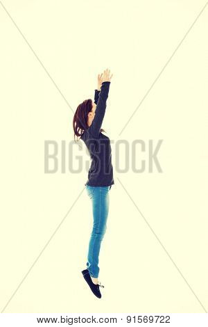 Pretty young woman jumping with hands up