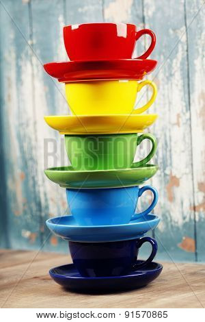 Colorful coffee cups on wooden table over blue background