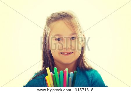 Pretty little girl holding crayons in hands