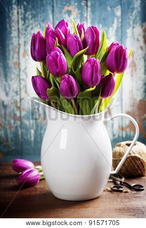 Purple Tulips, garden tools and easter eggs on a wooden surface. Studio photography