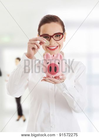Happy businesswoman putting coin to piggy bank.