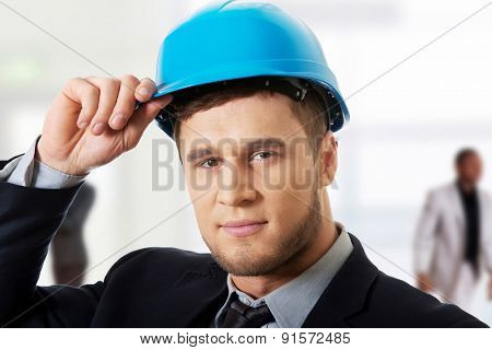 Happy handsome businessman with blue hard hat.