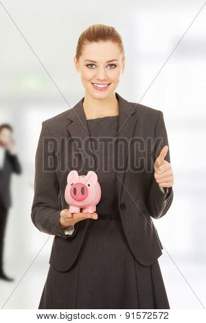 Business woman with piggybank and thumbs up.
