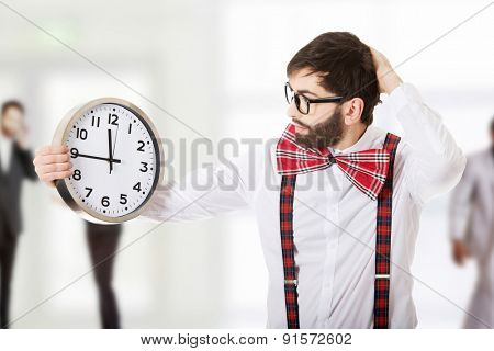 Worried man wearing suspenders holding big clock.