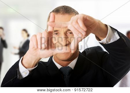 Mature businessman gesturing frame with hands.
