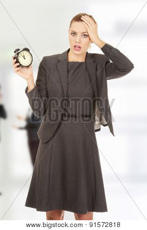 Beautiful shocked businesswoman with a clock.