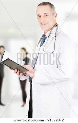 Handsome mature doctor man reading notes.