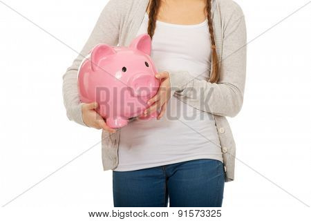 Casual teenage woman holding piggybank.