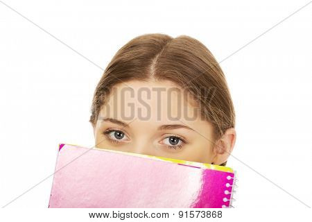 Casual teen woman hiding behind a notebook.