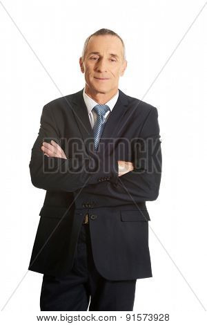 Mature businessman standing with folded arms.