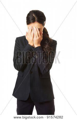 Businesswoman covering her face because of shame.