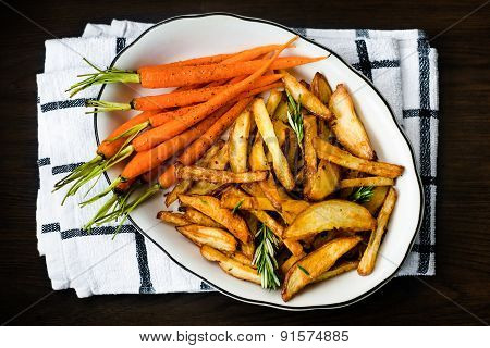 Roasted Vegetables Seasoned With Rosemary And Black Pepper. Oven-baked Baby Carrots And Potatoes