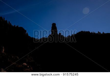 Sun Star on a Blue Sky over a Mountain Silhouette